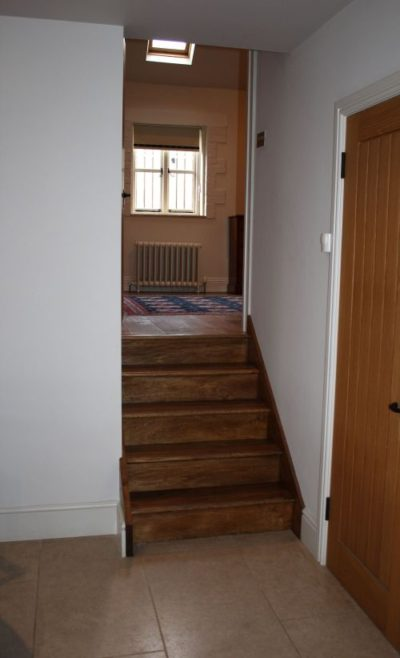 The Retreat - a short flight of wooden stairs from the kitchen to the upper ground floor